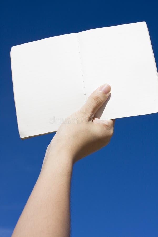 Рука на небе, держа книгу стоковое изображение