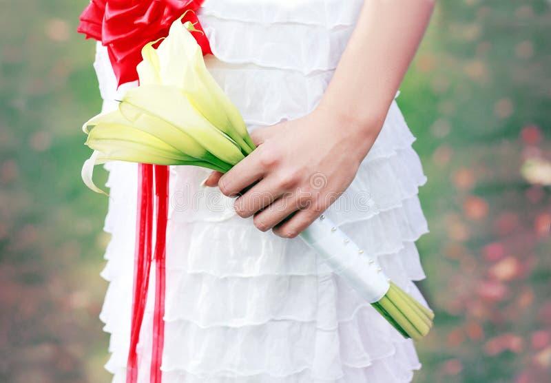 Рука невесты держа букет стоковое фото