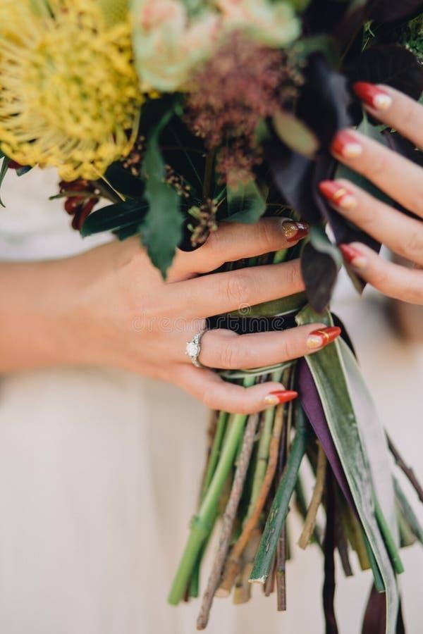 Рука невесты с красивым красным маникюром и роскошным кольцом с диамантами держит букет свадьбы Конец-вверх стоковые фотографии rf