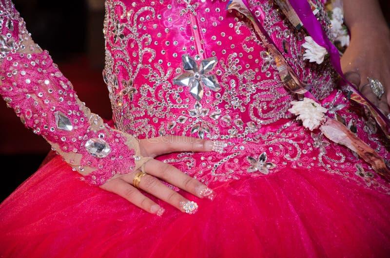 Рука невесты с обручальным кольцом в малиновом платье с пуком счетов NIS 200 и 100 стоковые фотографии rf