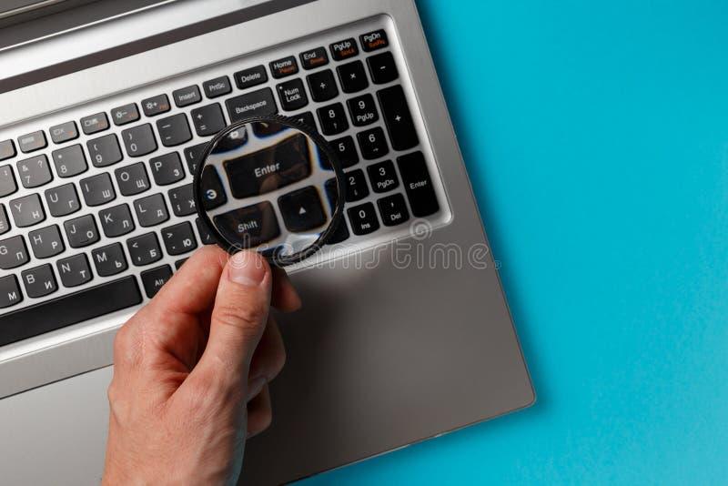 Рука ноутбука и человека с лупой на голубой предпосылке, концепции поиска стоковая фотография rf