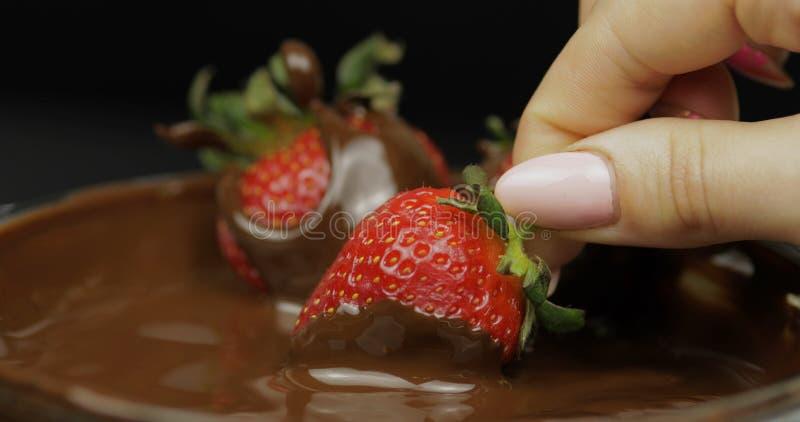 Рука окуная клубнику в расплавленном шоколаде Еда десерта свежих ягод сладкая стоковое изображение rf