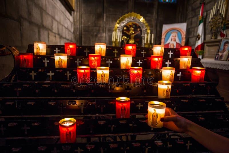 Рука освещая свечу в церков стоковая фотография