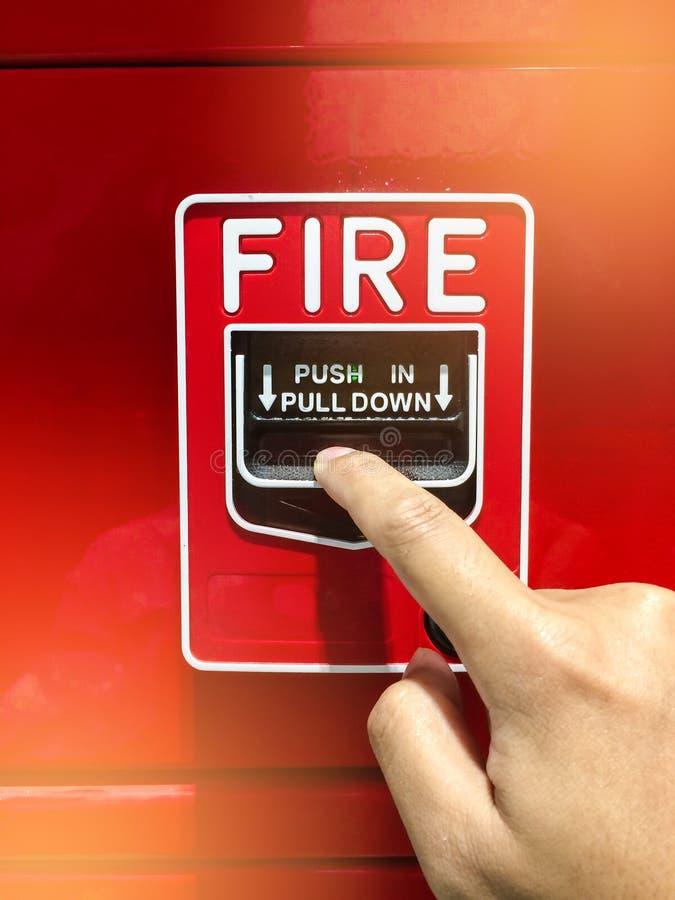 Рука достигая и вытягивая красный переключатель пожарной сигнализации потревожьте красный цвет пожара стоковая фотография rf