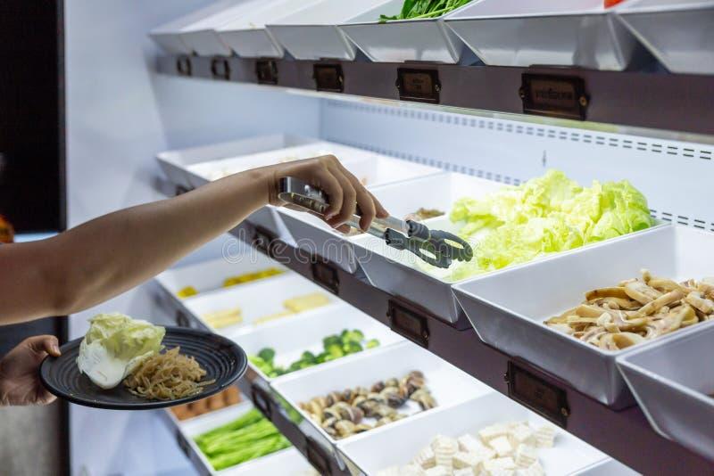 Рука отборная и сжимая свежие овощи в черной плите от линии еды для шведского стола sukiyaki в холодильнике стоковая фотография