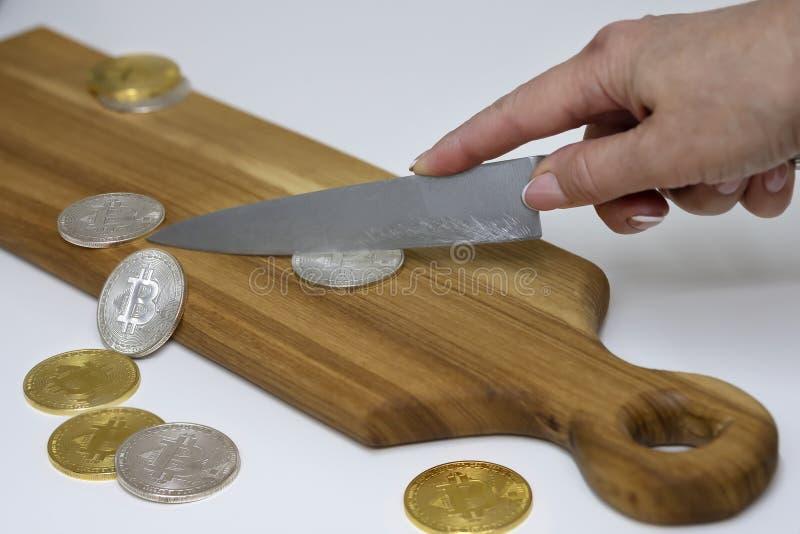 Рука отрезала bitcoin на разделочной доске, уменьшает цену, концепцию стоковые изображения rf