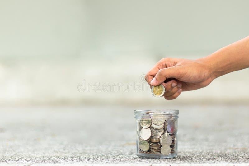 рука падает деньги в стеклянный опарник стоковое фото