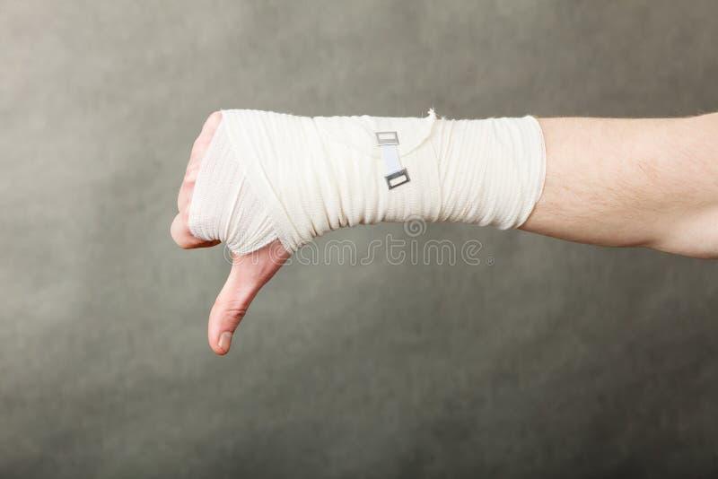 Рука перевязанная мужчиной с большим пальцем руки вниз подписывает стоковые фотографии rf