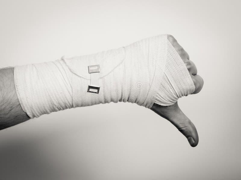 Рука перевязанная мужчиной с большим пальцем руки вниз подписывает стоковая фотография
