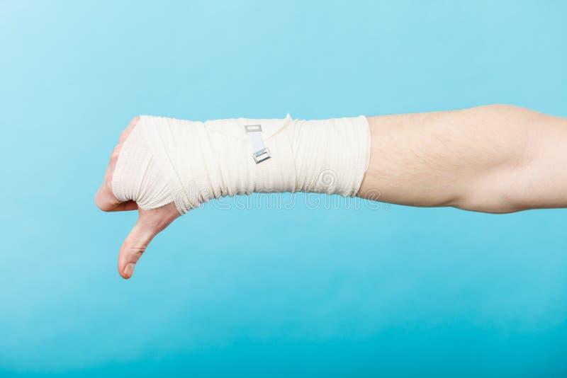 Рука перевязанная мужчиной с большим пальцем руки вниз подписывает стоковое изображение rf