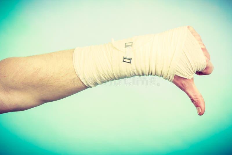 Рука перевязанная мужчиной с большим пальцем руки вниз подписывает стоковые изображения rf