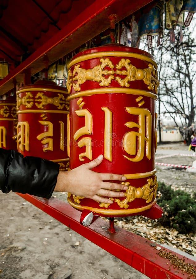 Рука переплетает барабанчики молитве на буддийском виске в St Petersbur стоковые изображения
