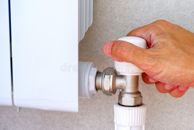 Рука персоны на регуляторе радиатора топления стоковое фото