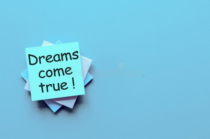 Рука пишет мечты приходит верно - на свете - голубая предпосылка с пустым космосом для текста и глумится вверх стоковая фотография