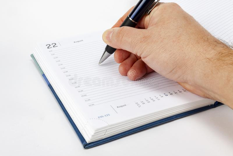 Рука пишет с ручкой в еженедельнике стоковые изображения rf