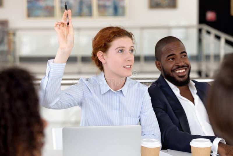 Рука повышения коммерсантки спрашивает вопрос на тренировке разнообразной группы корпоративной стоковое фото rf