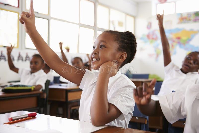 Рука повышения школьницы во время урока на начальной школе стоковые фотографии rf