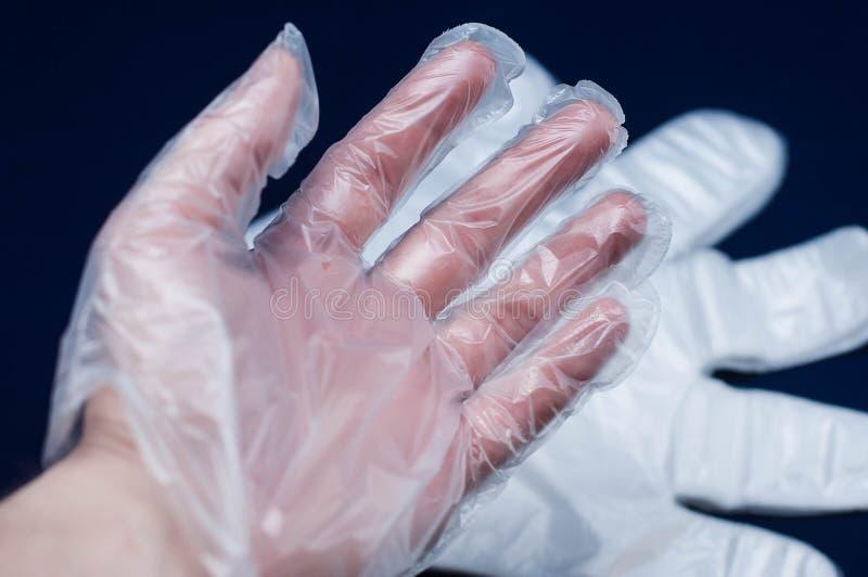 Рука подписывает внутри перчатки полиэтилена на темной предпосылке с хорошим освещением стоковые изображения rf