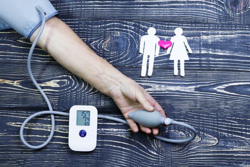 Рука пожилого монитора кровяного давления человека человек отрезанный из бумаги и красного сердца на деревянной предпосылке Ход,  стоковые изображения rf