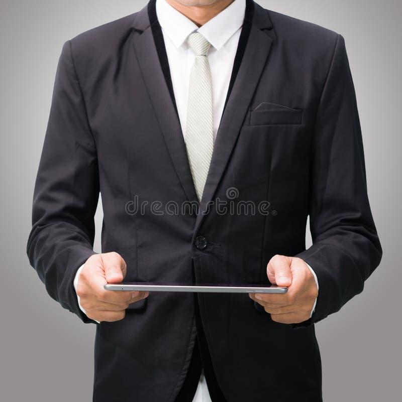 Рука позиции бизнесмена стоящая держа пустую таблетку стоковое фото