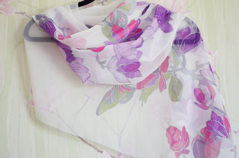 Рука покрасила шарф шелка на вешалке стоковое фото