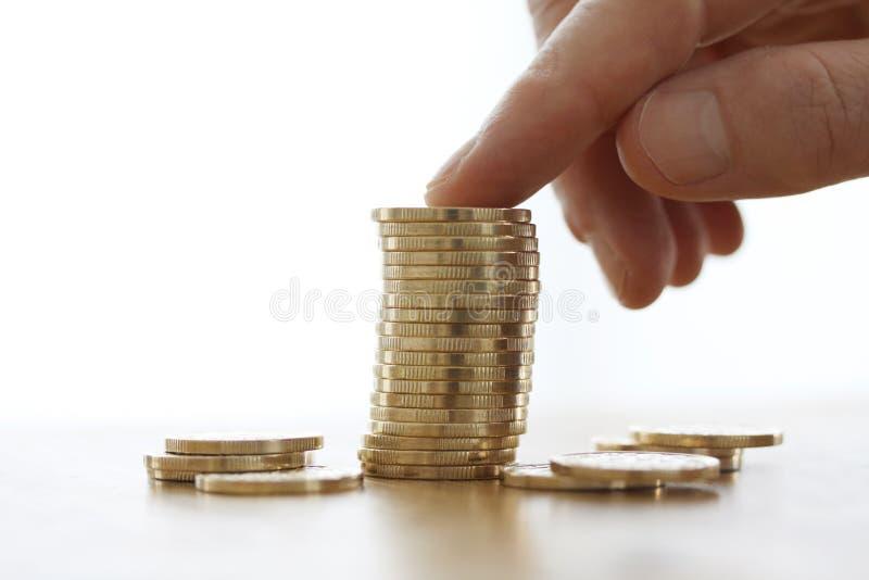Рука положила больше золотых монеток к стогу денег на белую предпосылку Конец-вверх руки кладя монетку к стогу монеток Финансы a  стоковая фотография