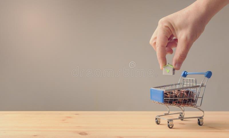 Рука положила бумажный дом в тележку вполне монеток, сбережений и loa стоковые изображения
