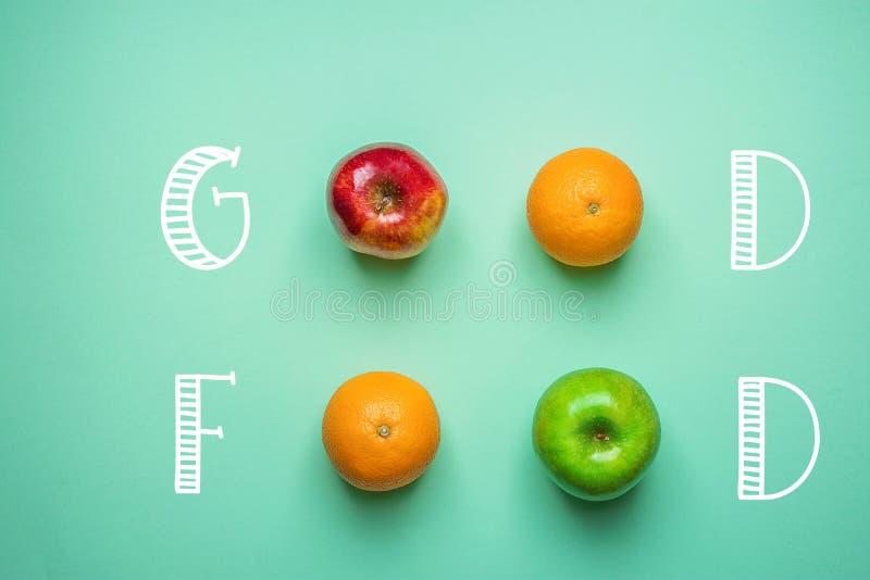 Рука помечая буквами хорошую еду на предпосылке бирюзы с яблоками красного цвета зеленого цвета апельсинов плодоовощей Здоровая ч стоковое изображение rf