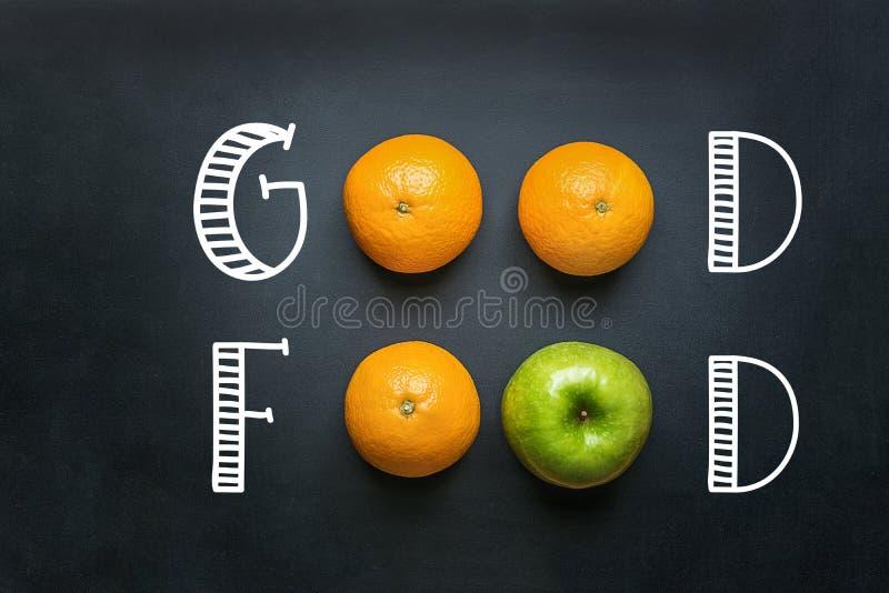 Рука помечая буквами хорошую еду на черной доске с апельсинами зеленым Яблоком плодоовощей Здоровая чистая энергия витаминов Vega стоковые изображения