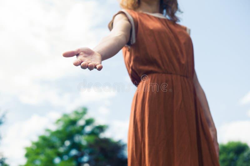 Рука помощи молодой женщины предлагая в природе стоковое фото