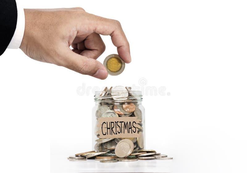 Рука положила монетку в стеклянный опарник, сохраняя деньги для рождества, на белой предпосылке стоковые фотографии rf