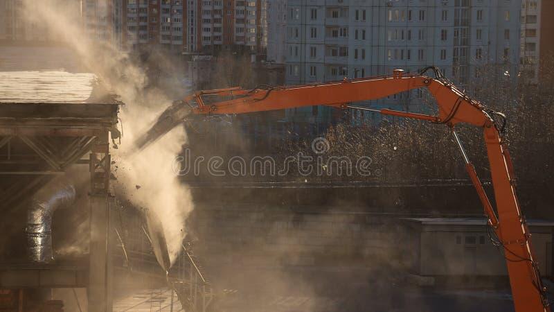 Рука подрыванием экскаватора в sunlit облаке пыли разбирает bui стоковые фотографии rf