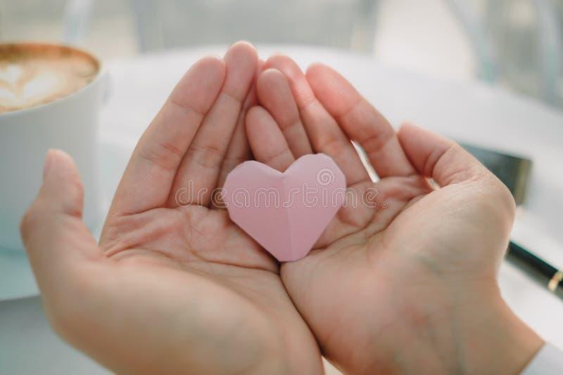 Рука предпосылки дня валентинки молодой женщины с бумажным сердцем I стоковое фото rf