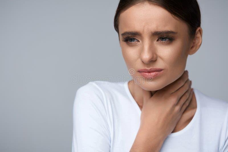 рука предпосылки изолированная над женщиной больной боли в горле места белой Больная женщина страдая от боли, тягостный заглатыва стоковое фото rf
