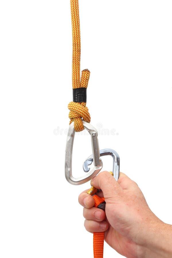 Рука прикрепляя фиксируя carabiner на других стоковое фото rf