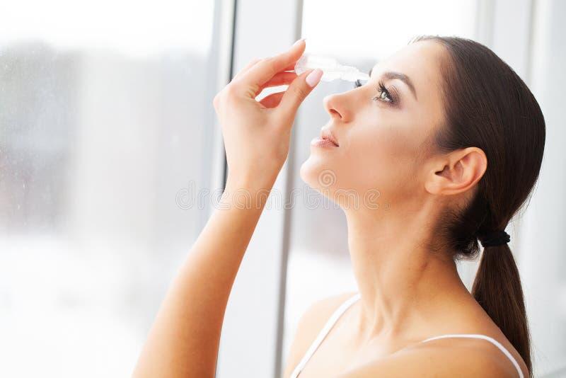 рука принципиальной схемы коммерсантки 3d указывая слово зрения Молодая красивая женщина с Eyedrops стоковая фотография rf