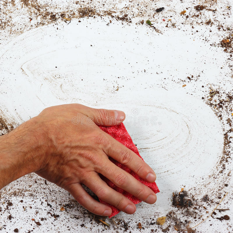 Рука при красная губка обтирая тяжело пакостную поверхность стоковое фото rf