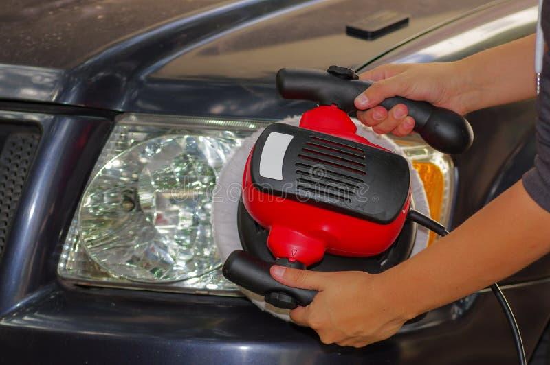 Рука при полировщик очищая фары автомобиля стоковое фото