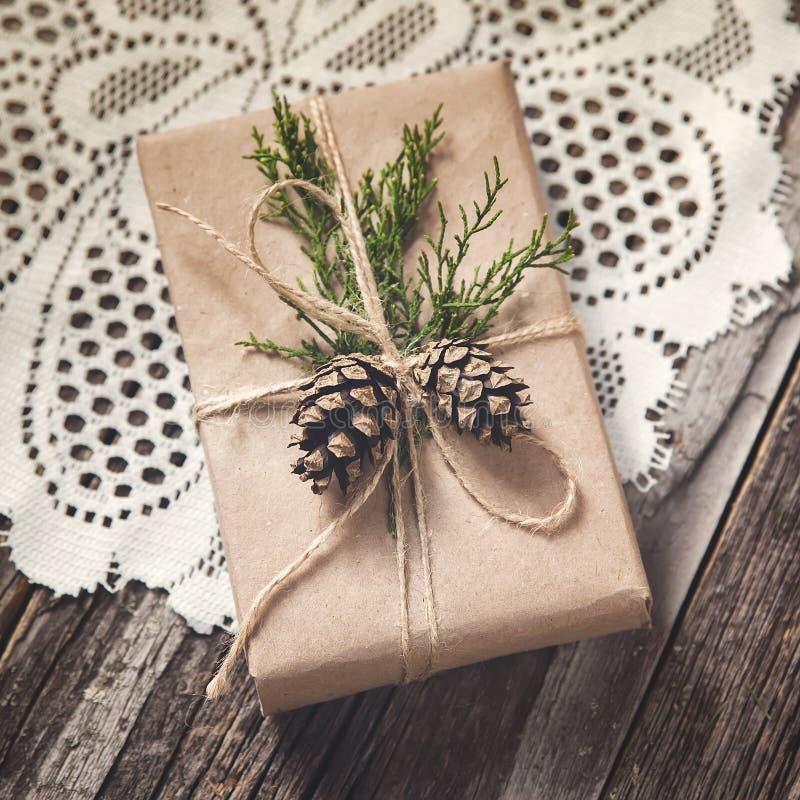Рука произвела подарок на деревенской деревянной предпосылке стоковое фото