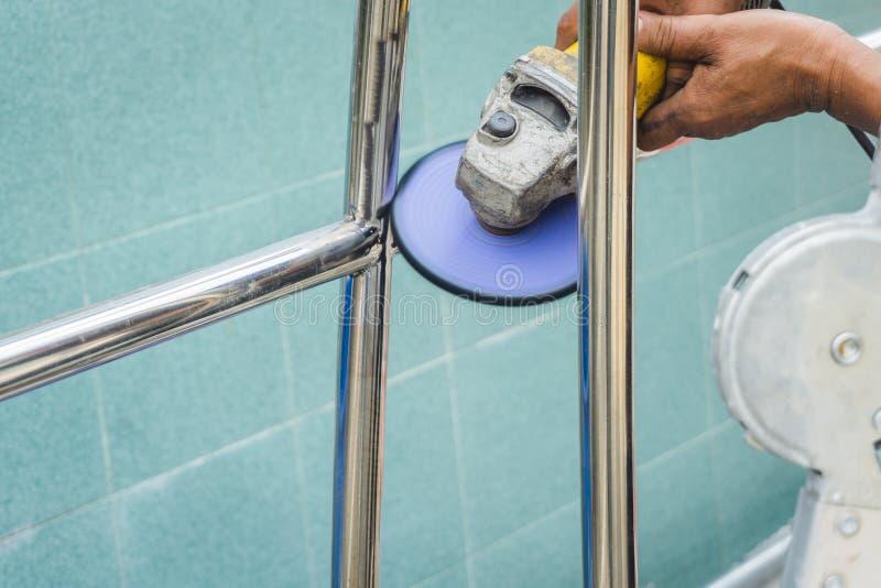 Рука работника подрядчика использует электрический инструмент точильщика с po стоковая фотография rf