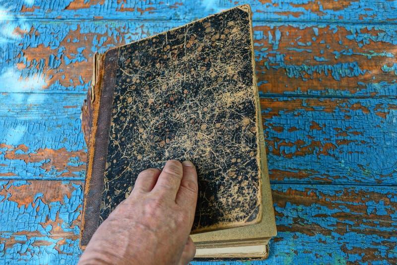 Рука раскрывает коричневую старую книгу на таблице стоковая фотография rf