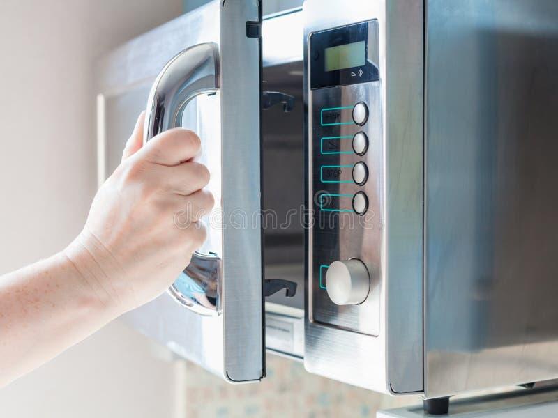 Рука раскрывает микроволновую печь для варить еду стоковое изображение