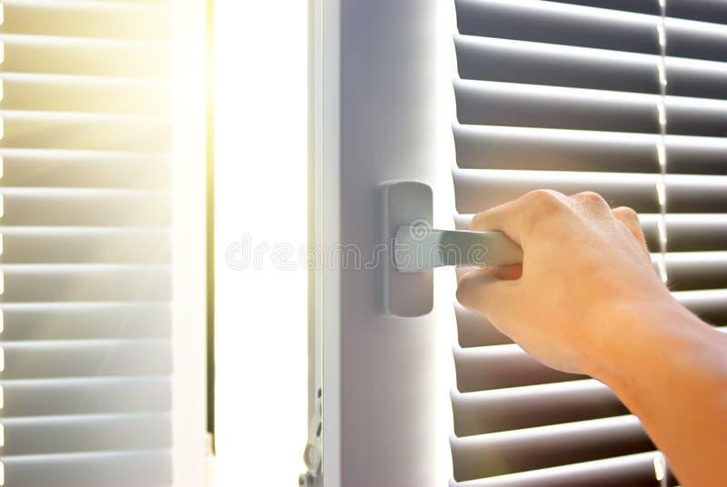 Рука раскрывает окно. стоковое изображение