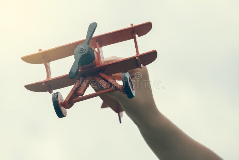 Рука ребенка держа деревянный handmade самолет стоковое фото rf