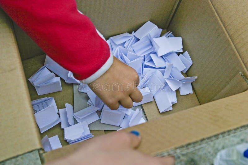 Рука ребенк выбирая билет лотереи стоковые изображения