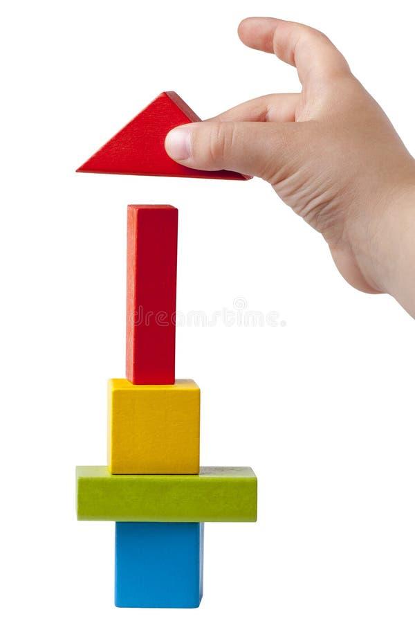Рука ребенк строя Multicolor изолированные кирпичи высокой башни стоковое изображение