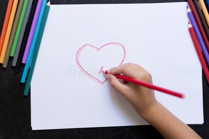 Рука ребенк с карандашем рисует сердце на белой бумаге Принципиальная схема дня ` s матери Торжество Ручной работы карта стоковые фотографии rf