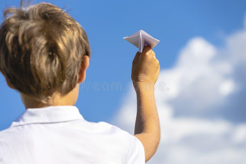 Рука ребенк с самолетом белой бумаги против голубого неба стоковое изображение rf
