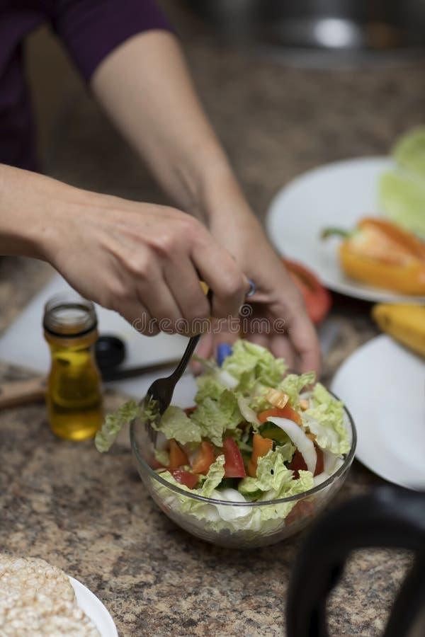 Рука режет овощи для салата в кухне стоковое фото rf