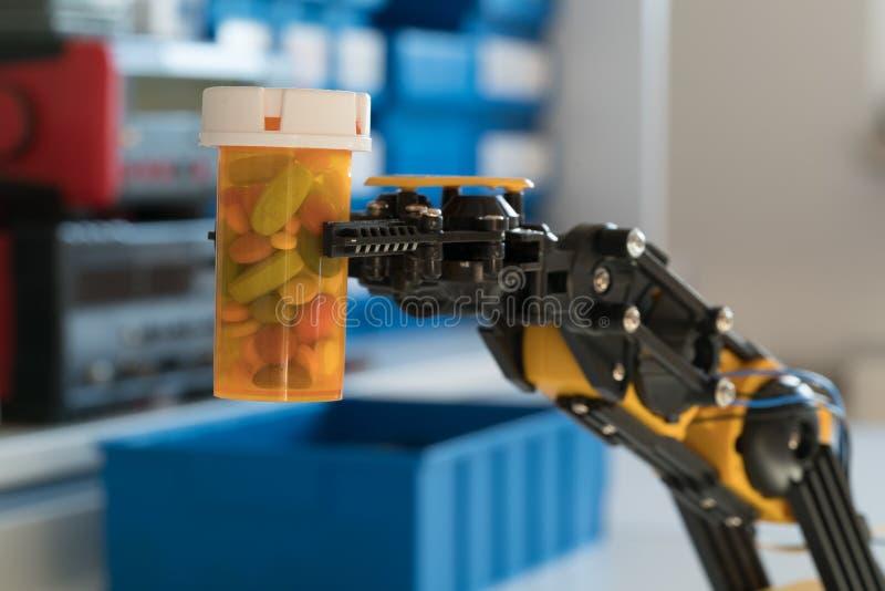Рука робота держит бутылку пилюлек стоковое изображение